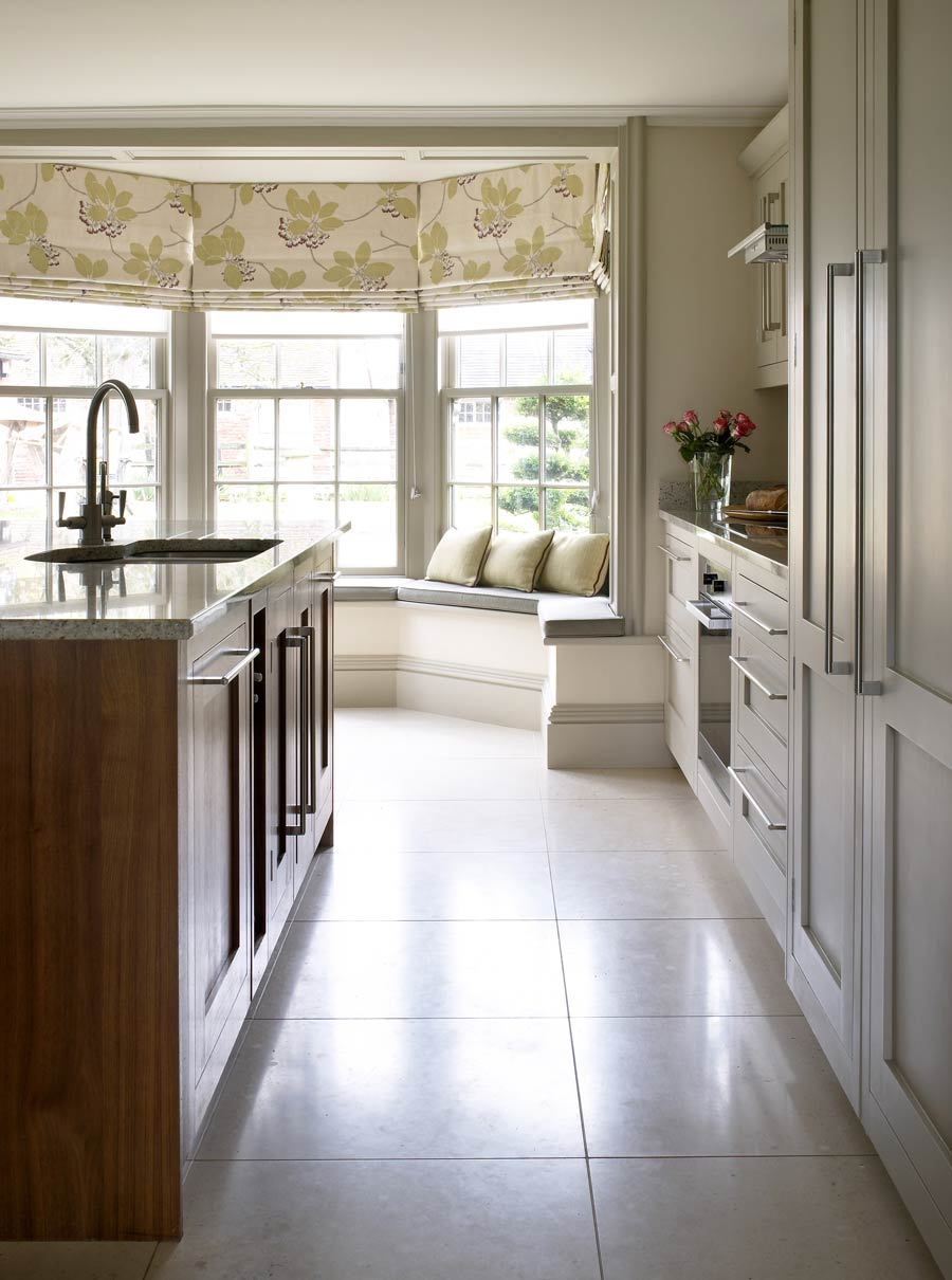 Classical kitchen design in Georgian Farmhouse showing central island and bay windowseat with contemporary floral roman blind.